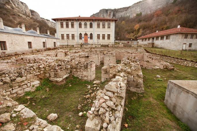 После того, как крымский хан покинул Чуфут-Кале, как столицу, первый дворец Ашлам, медресе (духовная школа), административные здания, хамам, были построены у самого подножия горы с пещерным городом, в местечке Салачик. Состоялась закладка нового города около 1500-1502 годов.