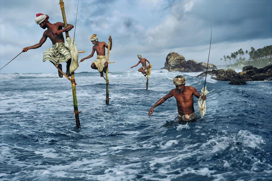 Местные жители здесь сидят со старинными приспособлениями для рыбалки